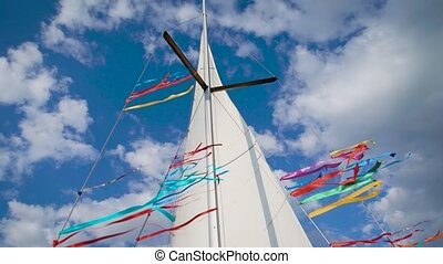 mast, white sail and multicolor tapes of sailing boat are on...