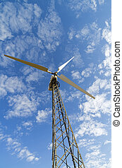Mast with wind power generator against the sky, view from below.