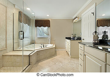 Master bath with cream colored cabinetry and glass slhower