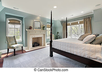 Master bedroom in luxury home with marble fireplace