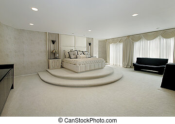 Master bedroom in luxury home with step up bed area