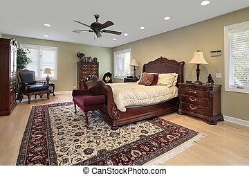 Master bedroom in luxury home with cherry wood bed