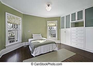 Master bedroom with green walls and dark wood flooring
