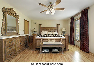 Master bedroom in luxury home with oak wood furniture