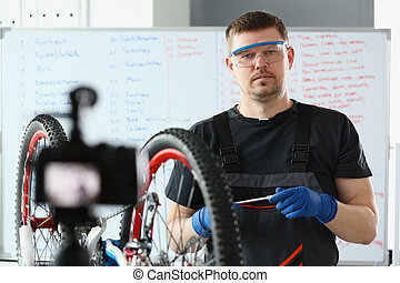 Master blogger demonstrates camera how to properly repair bicycle. Diy bike repair concept