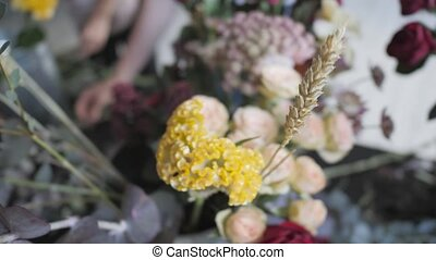 Master class of female florist at work with bunch of flowers. Girl making bouquet of various autumn flowers. Business woman florist at flower shop