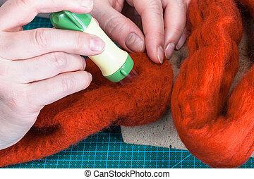 craftsman poking felt with felting punch close up