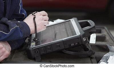 Master diagnostician checks data in diagnostic scanner.