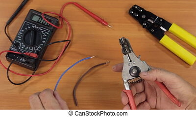 Master electrician removes insulation from copper wires with...