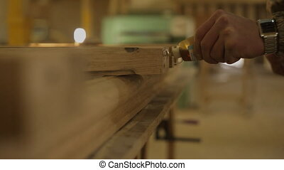 master glues a wooden product in the furniture workshop -...