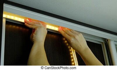 Master glues the LED strip on the metal profile of the cabinet,installation of decorative diode lighting High quality 4k footage