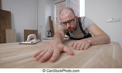 master is checking smoothness of polished surface of wooden...