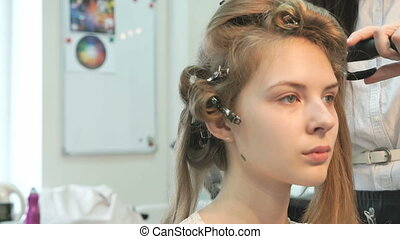 Master makes the curls to girl at the beauty salon - Master...
