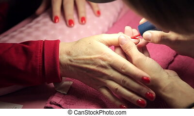 Master makes the girl manicure hands at salon
