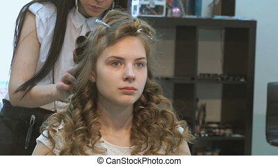 Master making hairstyle a girl at the beauty salon - Master...