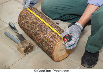 Master measures the length billet of logs on floor