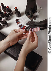 Master of manicure in black gloves, pick up with the client palette, preparation for applying gel Polish.