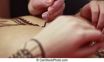 Master painting with henna on body of girl - Mehendi. Master...