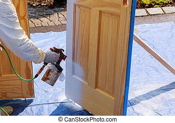 Master painting wood doors with spray gun processing...