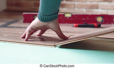 Master puts laminate floor - Master puts laminate on the...