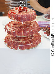 Master slicer decorating with  iberian cured ham cake stand with heart on top
