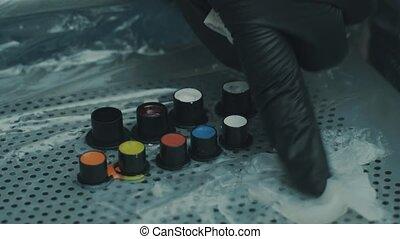 Master taking tattoo ink from a special jars - Master...