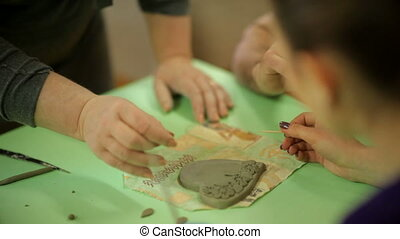 Master with students makes souvenirs from clay. Work process...