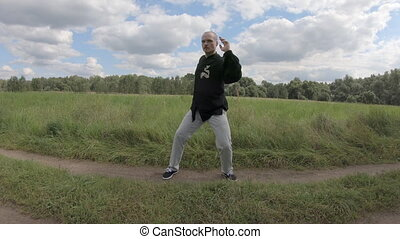 Tai Chi gymnastics. European man with a beard performs Eastern gymnastics exercises. Green nature all around, white clouds in the blue sky
