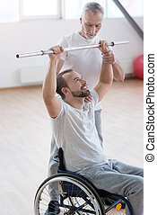 Masterful aged general practitioner training the disabled in the gym