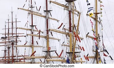 Masts of sailing ships stand with collected sails and flags...