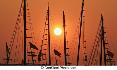 Masts of ships and boats at sunset. Time lapse.