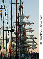 Masts of tall ships in a port in the evening