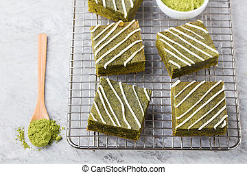 Matcha green tea brownie cake with white chocolate on a cooling rack Grey stone background