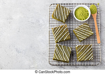 Matcha green tea brownie cake with white chocolate on a cooling rack Grey stone background Top view Copy space