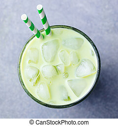 Matcha green tea ice latte in a glass. Grey stone background. Top view.