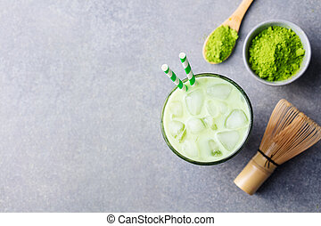 Matcha, green tea ice tea in glass. Grey stone background. Top view. Copy space.