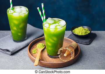 Matcha, green tea ice tea in tall glass on wooden plate. Grey stone background. Copy space.