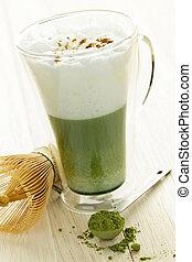Matcha green tea latte beverage in glass mug with whisk