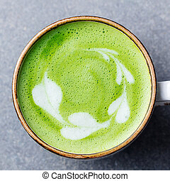 Matcha, green tea latte in a cup. Grey stone background. Close up. Top view.