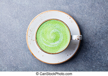 Matcha, green tea latte in a cup. Grey stone background. Top view.