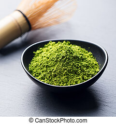 Matcha, green tea powder in black bowl with bamboo whisk on slate background. Close up.