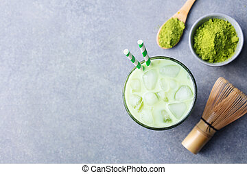 Matcha ice green tea in glass. Grey stone background. Top view. Copy space.