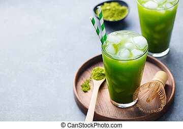 Matcha ice tea in tall glass on wooden plate. Grey stone background. Copy space.