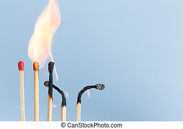 Matches in group burning safety-match with red, orange, yellow fire. Isolated on blue sky background