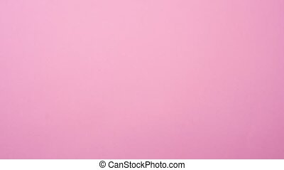 Top view of matching white rectangular jigsaw puzzle pieces on pink background, timelapse