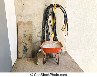 Material for repairs in an apartment is under construction remodeling rebuilding and renovation. The board, electric cables, a red wheel barrow and a large brick on the floor