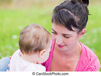 Maternal attachment - Portrait of an adorable baby girl with...