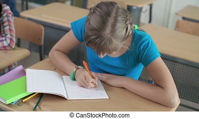Math Exam - High angle view of school girl doing sums in her...
