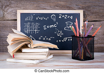 math formulas, education and knowledge concept. Stack of books and chalk blackboard