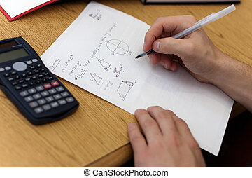 A young man working out mathematical equations on paper.